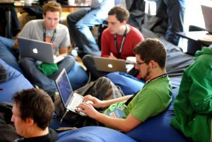 A group of men sit on beanbags working on their laptops