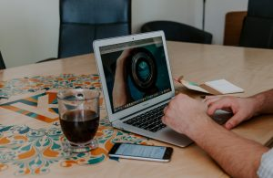 A man works at a laptop on a desk with a cup of coffee